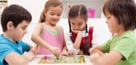 Children playing board game - sitting around a small table